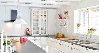 L-shaped, countr-house-style kitchen with white cabinets and grey worksurface in Scandinavian wooden house