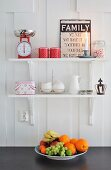 Sign with motto, scales and favourite crockery on white shelves above bowl of fruit in Scandinavian country-house kitchen