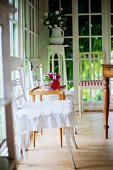 Traditional kitchen chairs painted white in front of floor-to-ceiling lattice windows