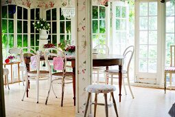 Thonet chairs with white, peeling paint around antique wooden table in conservatory