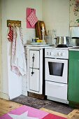 Solid-fuel stove, cooker and tea towels hanging from wall hooks in corner of kitchen