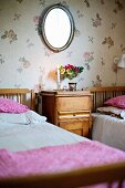 Wood-framed twin beds and matching bedside cabinet against floral wallpaper in rustic bedroom