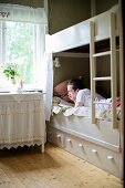 Teenager lying on white wooden bunk bed next to side table with valance below window