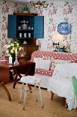 Various chairs, wooden table, sofa, crockery in open corner cabinet and floral wallpaper