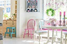 Vintage-style, white dining set, open doorway leading to kitchen, pink-painted chair in corner