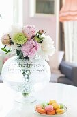 Bouquet in glass vase with etched pattern and plate of colourful macaroons on white table