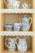 Rustic-style, white crockery with blue painted patterns on shelves with lace trim