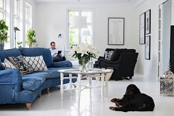 Curved sofa with denim upholstery and tray table in living room; black dog lying on white-tiled floor in foreground