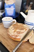 Cut loaf and knife on wooden board and blue and white ceramic crockery