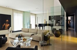 Glass partition in lounge area, pale sofa and plexiglas coffee table by Emmanuel Babled in modern interior
