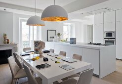 Open-plan, bright kitchen with modern table below pendant lamps with white and gold lampshades