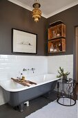 Free-standing vintage bathtub and side table with wrought iron frame in bathroom with grey walls and white tiling