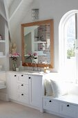 Bathroom with white washstand and bench below framed mirror and arched window