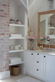 White fitted shelving and custom-made washstand below framed mirror on wall in corner of bathroom