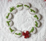 Circle of festively iced cupcakes on white surface