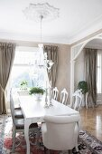 White armchairs and chairs with carved backrests around table in open-plan dining area of villa