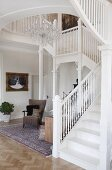 Staircase with white-painted, wooden balustrade in foyer of villa