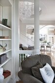 Armchair next to shelves and in front of white balustrade with white column