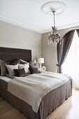 Box-spring bed with brown valance and stacks of scatter cushions against headboard in traditional bedroom with chandelier hanging from stucco ceiling rose