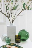 Branches of leaves in white ceramic vase and green drinking glass between two green glass spheres on white table