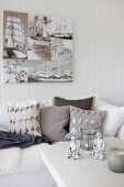 Coffee table in front of sofa with scatter cushions below photos printed on canvas on white, wood-clad wall