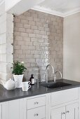 Kitchen counter with sink, black worksurface and pale grey, tiled splashback