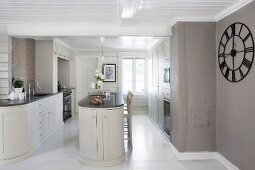 Open-plan, designer kitchen with free-standing counter and large clock on wall painted warm grey