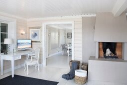 Desk in corner and open fireplace flanking wide doorway with view into dining room