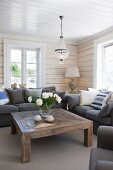 Rustic, solid wood coffee table and dark grey sofa in corner of rustic living room with wood-clad walls and ceiling