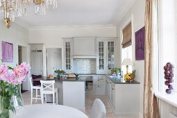 Dining set in open-plan, country-house kitchen with pale grey fronts and bar stools around island counter