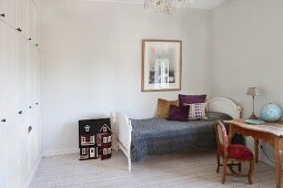 Desk next to single bed with antique, white frame in simple bedroom with fitted wardrobes