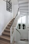 Rustic stairwell with winding staircase, white balustrade and pictures on wall