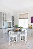 Island counter and white bar stools in open-plan, country-house kitchen