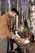 Man chopping vegetables on table in woods