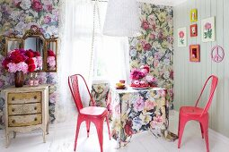 Floral wallpaper, matching tablecloth and pink, retro, metal chairs; peonies on vintage cabinet and vanity mirror to one side