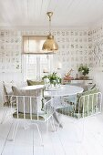 White metal chairs with cushions at round table in dining room with botanical wallpaper and white wooden floor
