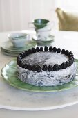 Marbled cake topped with blackberries on marble lazy Susan on dining table