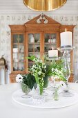 White flowers and lit candles in candlesticks on table in front of antique, glass-fronted cabinet