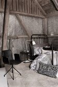 Bedroom in various shades of grey in barn-style interior with armchair, metal bed and half-timbered walls with wallpaper panels