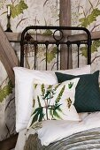 Green and white scatter cushion on black metal bed against half-timbered wall with wallpapered panels with botanical pattern