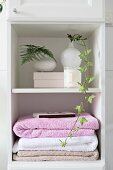 Stacked towels and foliage in white vases on bathroom shelves