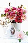 Nostalgic arrangement with vase of dahlias & snow globe on table