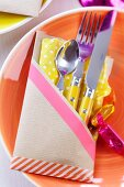 Hand-crafted kraft paper cutlery pocket stuck together with washi tape