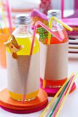 Bottles of pop decoratively wrapped in brown paper on felt coasters