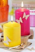Bunte Kerzen auf Packpapier-Untersetzern dekoriert mit ausgestanzten Schmetterlingen
