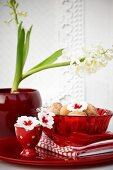 Miniature doughnuts in red glass bowl on table decorated with primula flowers & hyacinths