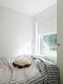 Window with roller blind at foot of bed, floral, ruched scatter cushions on striped grey cover