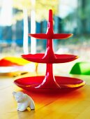 Bright red cake stand and small animal ornament on dining table
