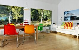 Colourful shell chairs and wooden table in front of panoramic window with woodland view; sofa with brightly striped scatter cushions to one side