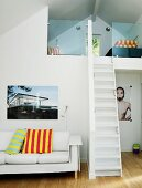 White couch with striped scatter cushions and large-format photographs flanking narrow, steep stairs leading to mezzanine under sloping ceiling